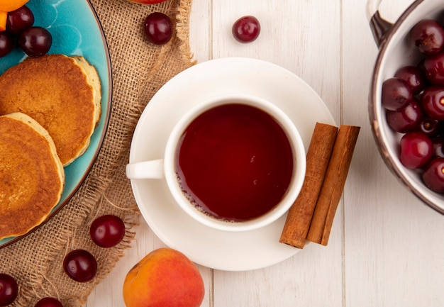 Nahaufnahme der tasse tee und zimt auf untertasse und pfannkuchen mit kirschen in teller und aprikosenkirschen auf sackleinen und schüssel kirschen auf holzhintergrund