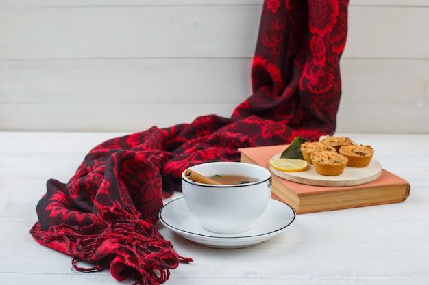 Nahaufnahme der tasse tee, weiße kekse in einem teller mit rotem schal und einem buch