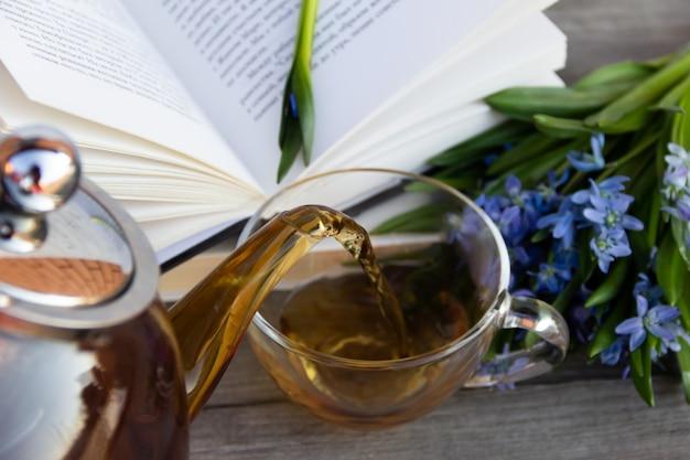 Nahaufnahme der teekanne, der tasse tee und des offenen buches auf hölzernem hintergrund. tee fließt aus der teekanne.