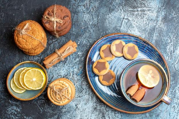 Nahaufnahme der teezeit mit verschiedenen keksen und hand, die eine tasse schwarzen tee hält