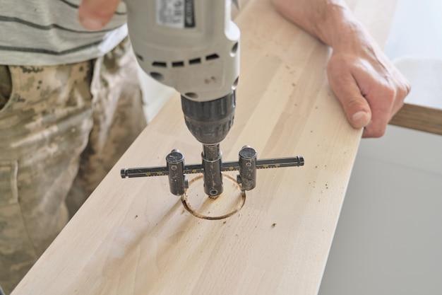 Nahaufnahme der tischlerhand unter verwendung der professionellen holzbearbeitungselektrowerkzeuge