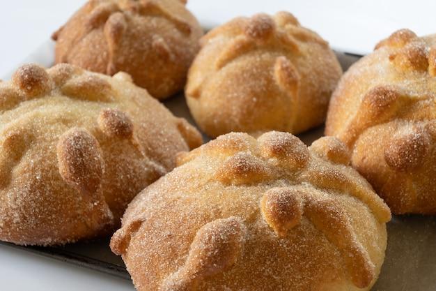 Nahaufnahme der traditionellen mexikanischen pan de muerto mit zucker und zimt auf weißem hintergrund, fokus auswählen, dia de muertos-konzept