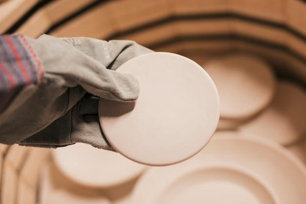 Nahaufnahme der tragenden handschuhe der frau hand, die keramische platten halten