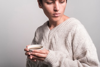 Nahaufnahme der tragenden Strickjacke der jungen Frau, die Kaffeetasse hält
