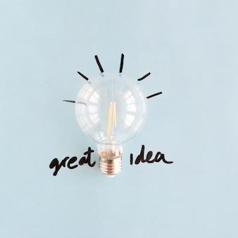 Nahaufnahme der transparenten glühlampe mit großem ideenwort auf blauem hintergrund