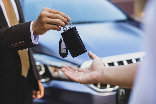 Nahaufnahme der übergabe des autoschlüssels vom autoverkauf an den besitzer