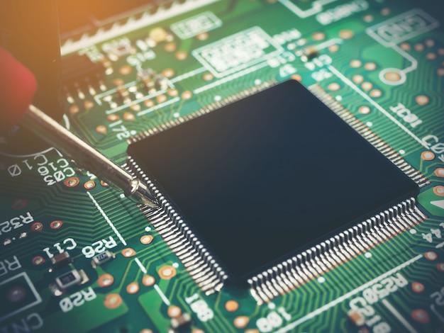 Nahaufnahme der überprüfung elektronischer pcb (leiterplatte) mit mikrochips-prozessortechnologie