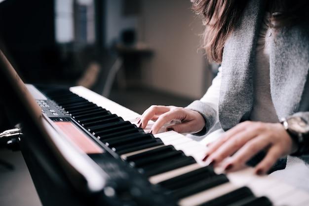 Nahaufnahme der unerkennbaren weiblichen person, die klavier spielt.
