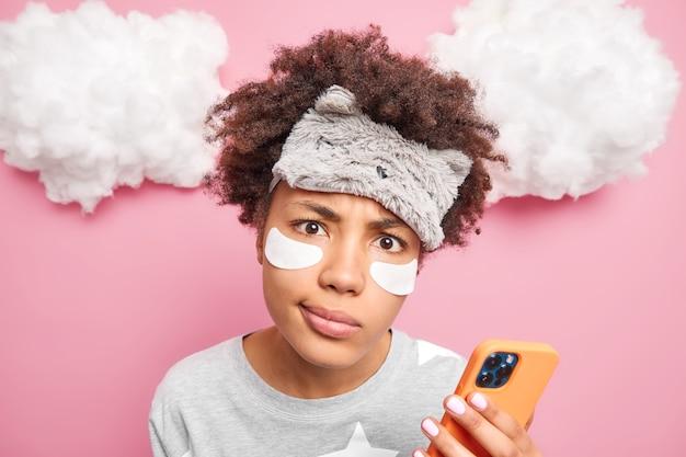 Nahaufnahme der unzufriedenen frau benutzt handy, bevor sie schlafen geht, trägt schlafmaske beauty patches pyjama macht schönheitsverfahren findet notwendige informationen im internet