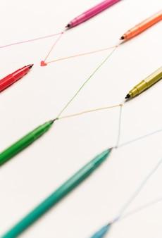 Nahaufnahme der verbundenen linien, die mit bunten markierungen auf weißem papier gemalt werden. linien für diagramme, zeitplan