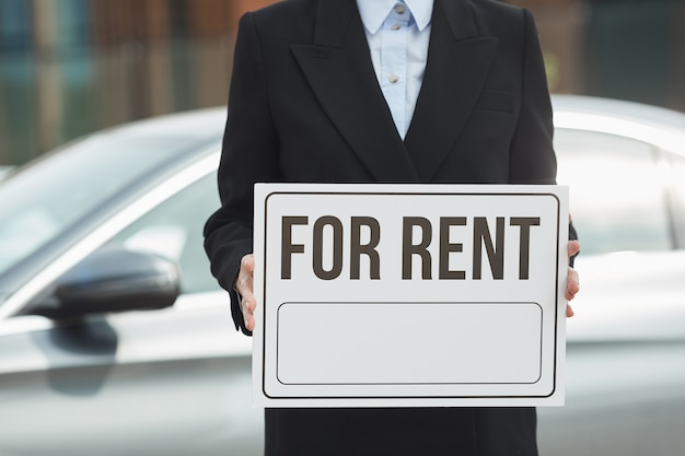 Nahaufnahme der verkäuferin im anzug, die plakat für miete in ihren händen mit auto im hintergrund hält