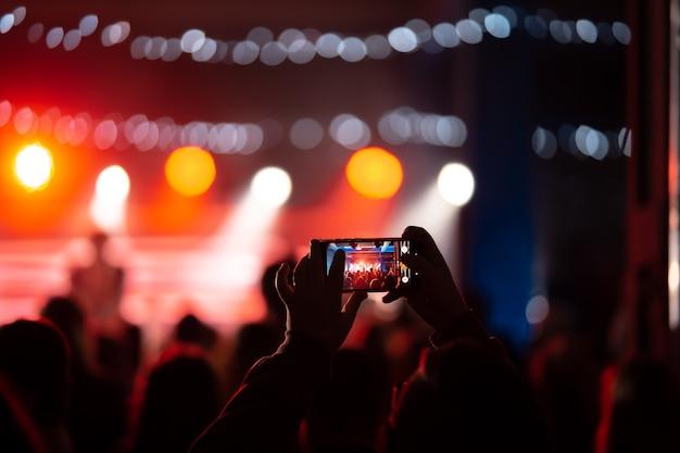 Nahaufnahme der videoaufnahme mit smartphone während eines konzerts. getöntes bild
