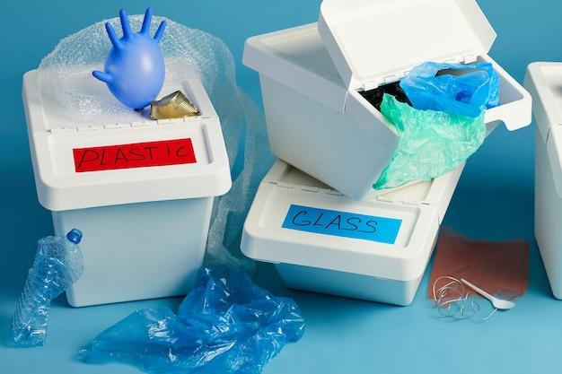 Nahaufnahme der vollen mülleimer für plastik- und papierabfälle in reihe, sortier- und recyclingkonzept