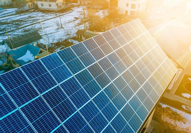 Nahaufnahme der von der sonne beleuchteten blauen glänzenden solar-photovoltaik-panels auf dem dach des gebäudes. erneuerbares ökologisches grünes energieproduktionskonzept.