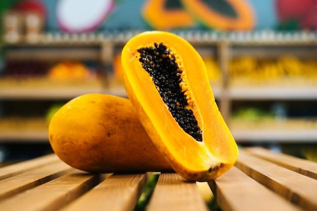 Nahaufnahme der vorderansicht der frischen saftigen papaya, die auf einer holzpalette im obst- und gemüsebereich steht