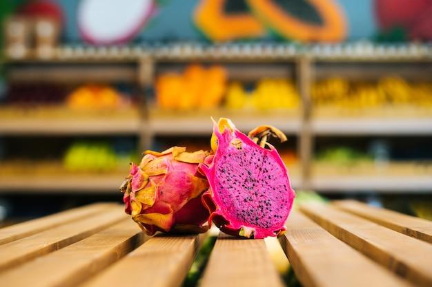 Nahaufnahme der vorderansicht von frischem saftigem pitahaya, das auf einer holzpalette im obst- und gemüsebereich steht