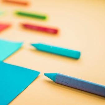 Nahaufnahme der wachszeichenstiftfarbe und des kartenpapiers gegen gelben hintergrund