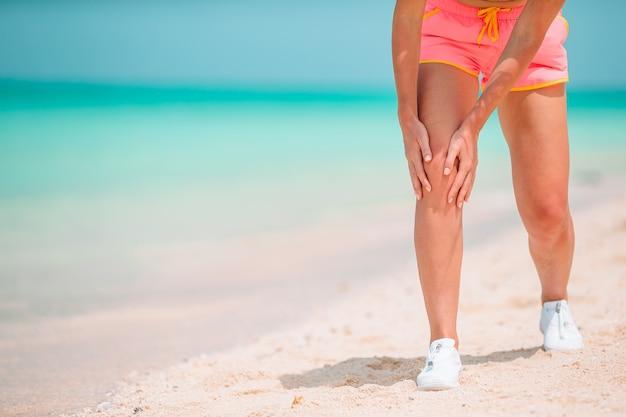 Nahaufnahme der weiblichen beine in den turnschuhen, die auf weißem sandstrand laufen