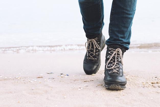 Nahaufnahme der weiblichen beine in den winterstiefeln sind auf dem strand