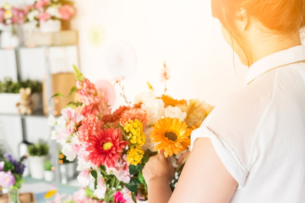 Nahaufnahme der weiblichen floristenhand, die bunte blumen anordnet