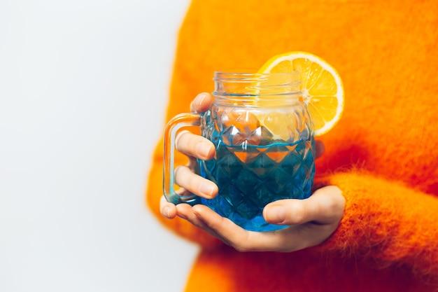 Nahaufnahme der weiblichen hände, die blaue glasschale mit saft und zitronenstück halten. tragen eines orangefarbenen pullovers.