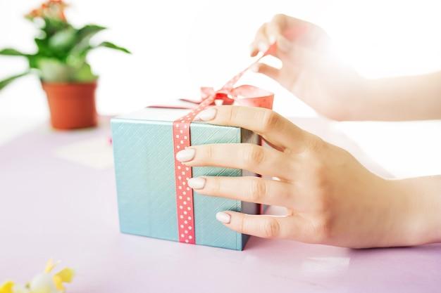 Nahaufnahme der weiblichen hände, die ein geschenk halten. schenken sie ein geschenk. blume im blumentopf. präsentieren sie in der nähe von brief und blume. weibliche hand