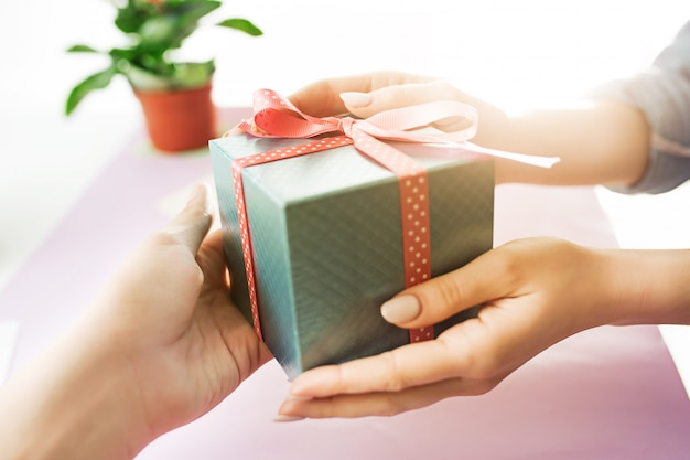 Nahaufnahme der weiblichen hände, die ein geschenk halten. trendiger rosa schreibtisch.