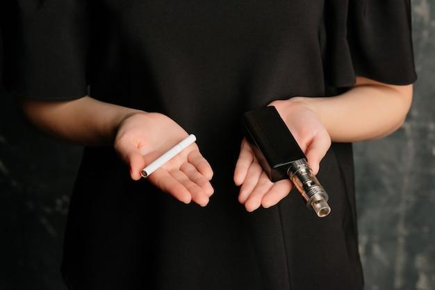Nahaufnahme der weiblichen hände, die eine e-zigarette in einer hand und nikotin-zigarette in einer anderen hand halten. auswahlkonzept. unterschiede in geschmack und vorlieben