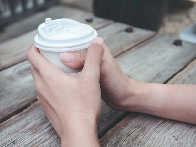 Nahaufnahme der weiblichen hände, die eine weiße kaffeetasse auf holztisch halten. junge frau, die kaffee aus der einwegschale trinkt.