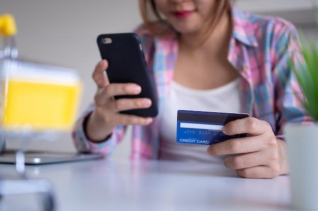 Nahaufnahme der weiblichen hände, die kreditkarte und smartphone halten. frau, die online bezahlt, bankdienstleistungen nutzt, informationen eingibt, rechnungen bezahlt, einkaufskonzept.