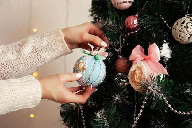 Nahaufnahme der weiblichen hände hängen den ball am baum. weihnachtsdekoration, spielzeug, das am baum hängt, weihnachtsbaumkugel.