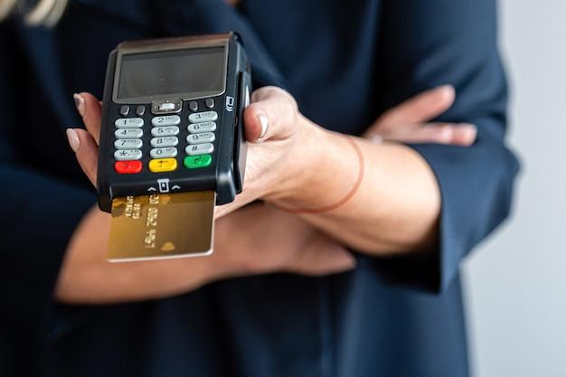 Nahaufnahme der weiblichen hände halten terminal für die zahlung durch bargeldloses geld