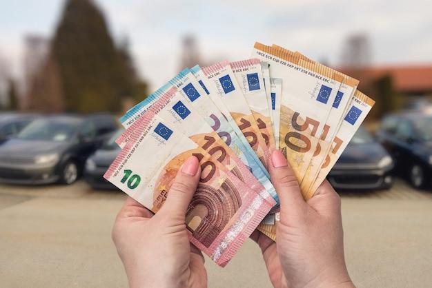 Nahaufnahme der weiblichen hände mit euro-banknoten auf autoshow