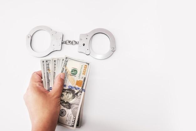 Nahaufnahme der weiblichen hände mit handschellen gefesselt und dollarnoten auf weiß halten. platz kopieren. korruptions- und bestechungskonzept