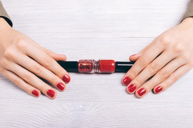 Nahaufnahme der weiblichen hände mit roter maniküre und flaschen mit lack