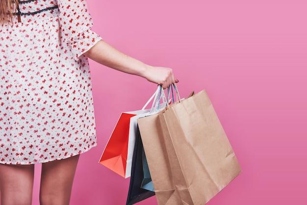 Nahaufnahme der weiblichen hand, die bunte einkaufstaschen auf rosa hält