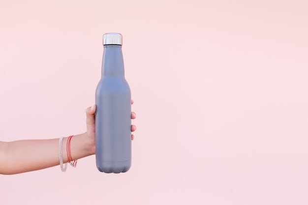 Nahaufnahme der weiblichen hand, die eine wiederverwendbare stahl-öko-thermo-wasserflasche der blauen farbe hält. pastellhintergrund der rosa farbe. sei plastikfrei. kein verlust.