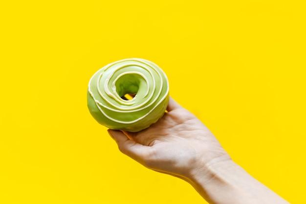 Nahaufnahme der weiblichen hand, die grünen donut auf gelb hält