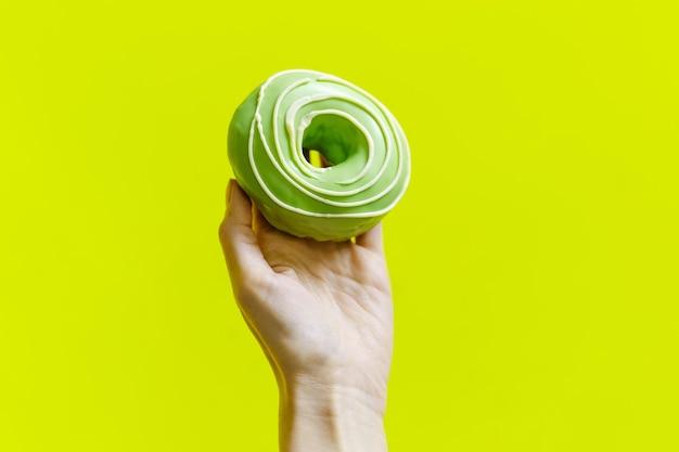 Nahaufnahme der weiblichen hand, die grünen donut auf hellgrün hält