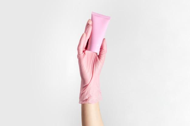 Nahaufnahme der weiblichen hand, die handschuh trägt, die kosmetische röhre der pastellkorallenrosa-farbe hält, lokalisiert auf weißem studiohintergrund.