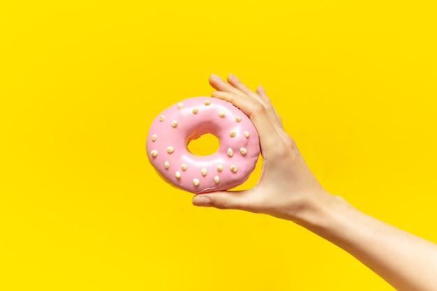 Nahaufnahme der weiblichen hand, die rosa donut auf gelb hält
