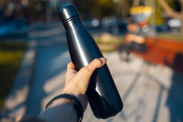 Nahaufnahme der weiblichen hand, die stahlthermowasserflasche des schwarzen hält. öko-mehrwegflaschen aus metall ohne abfall. hintergrund der verschwommenen straße.