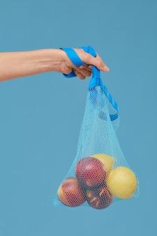 Nahaufnahme der weiblichen hand, die tasche mit früchten lokalisiert auf blauem hintergrund hält