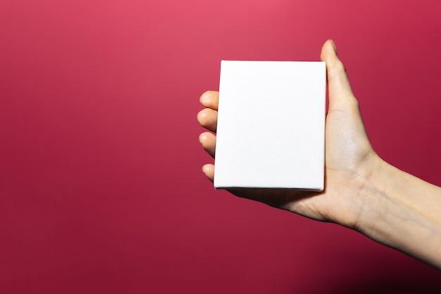 Nahaufnahme der weiblichen hand, die weißes papier mit modell auf oberfläche der rosa korallenfarbe hält