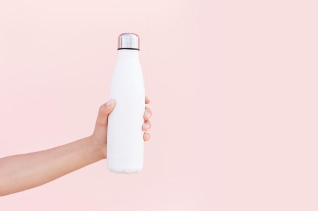Nahaufnahme der weiblichen hand, die wiederverwendbare, stahl-öko-thermo-wasserflasche von weiß hält, lokalisiert auf hintergrund der pastellrosa farbe mit kopienraum. sei plastikfrei. kein verlust. umweltkonzept.
