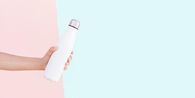 Nahaufnahme der weiblichen hand, die wiederverwendbare stahlthermowasserflasche hält