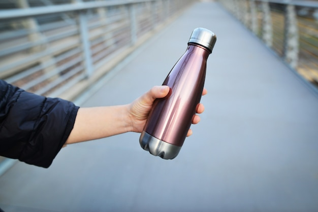 Nahaufnahme der weiblichen hand, die wiederverwendbare, thermisch glänzende stahlflasche für wasser hält.