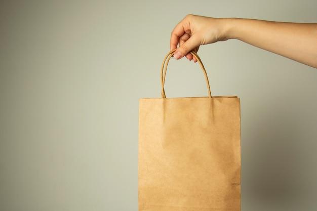 Nahaufnahme der weiblichen hand kraftpapierpaket halten, designspott oben. null easte konzept.