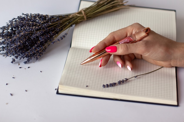 Nahaufnahme der weiblichen hand mit der schönen maniküre, die goldenen rosa glänzenden stift auf dem karierten notizbuch mit blumenstrauß des lavendels hält