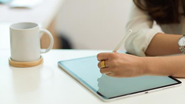 Nahaufnahme der weiblichen hand mit digitalem tablet mit stylus-stift auf weißem tisch mit kaffeetasse